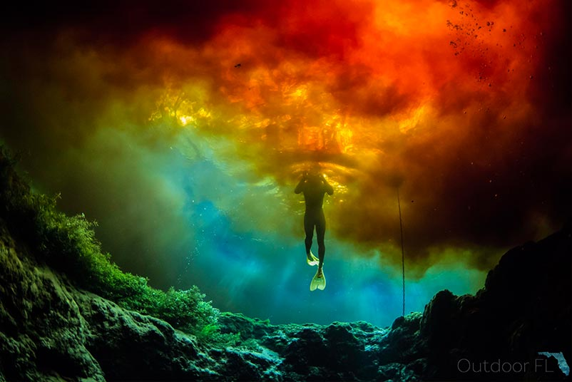 An underwater photograph taken below a snorkeling photographer surrounded by streaks of red, orange, yellow, green and blue in Gainesville, Florida