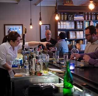 A bartender pours a glass of red wine for a customer at the bar in The Grey Plume in Omaha, Nebraska