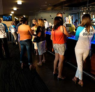 Meeting attendees gather at a wooden bar with a glowing blue top in Omaha, Nebraska