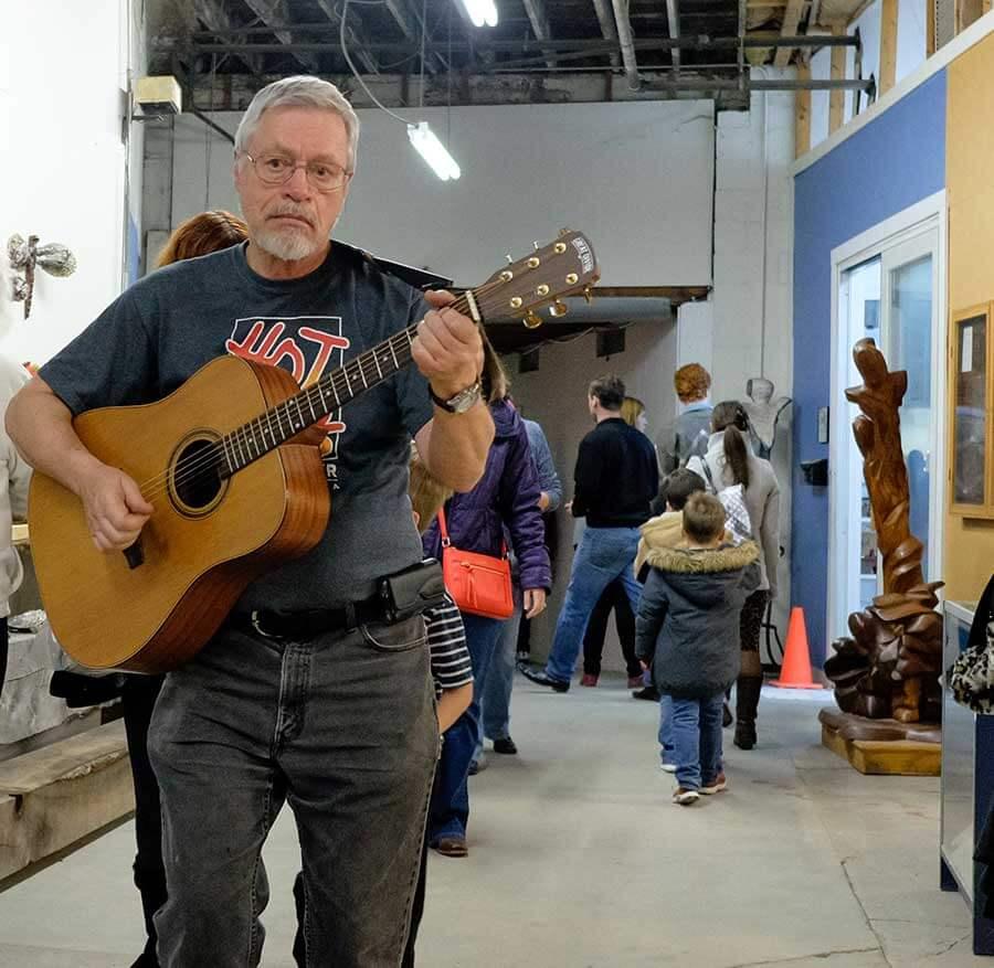A man strums a guitar at Hot Shops in Omaha, Nebraska