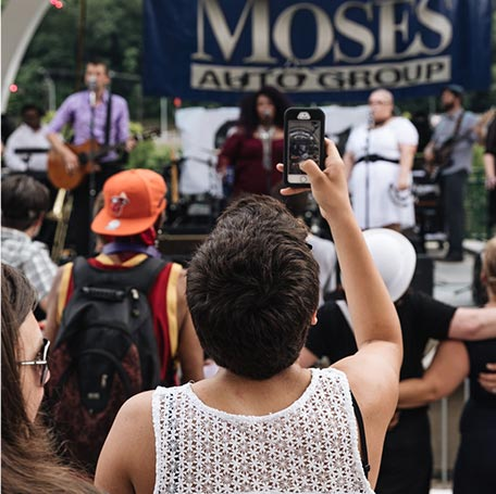 Concert-goer taking phone photo of band playing at Live on the Levee in Charleston, West Virginia
