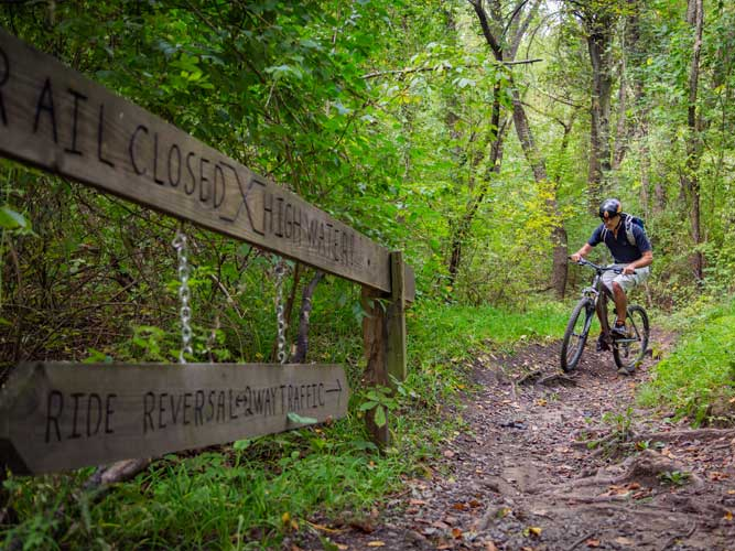 A man bikes toward a wooden sign at Imagination Glen in Indiana Dunes, Indiana