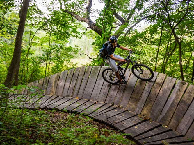 A man bikes a steeply angled wooden walkway at Imagination Glen in Indiana Dunes, Indiana