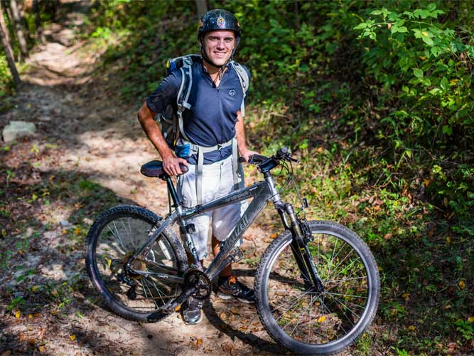 A man stands next to his mountain bike at Imagination Glen in Indiana Dunes, Indiana