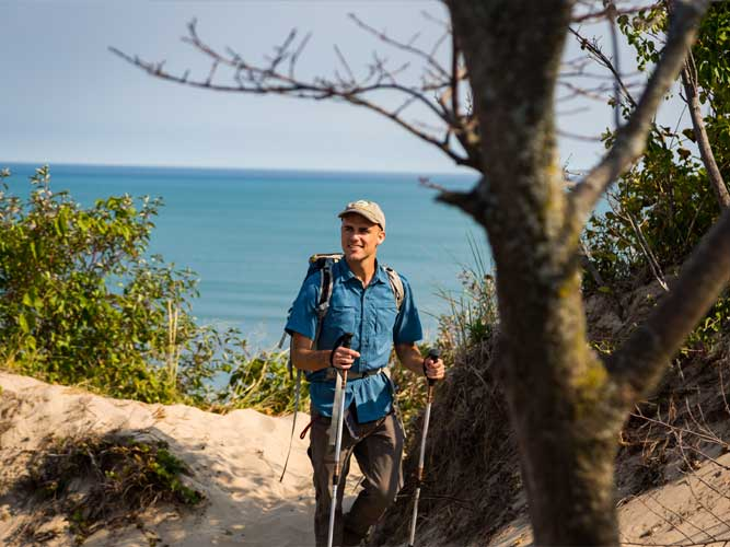 With Lake Michigan in the background, a man hikes the sand dunes in Indiana Dunes, Indiana