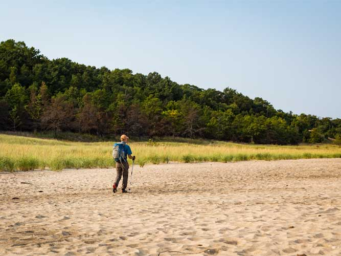 A man hikes across sand in Indiana Dunes, Indiana