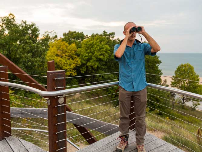 A man looks through binoculars in Indiana Dunes, Indiana