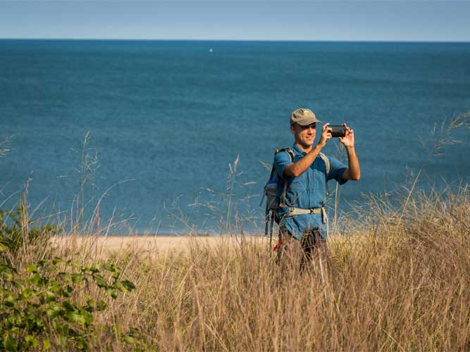 A man stands on a sand dune looking over the beach and Lake Michigan through binoculars in Indiana Dunes, Indiana