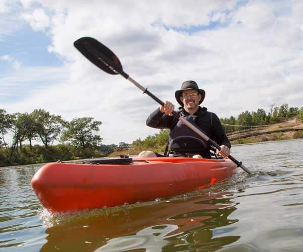 A man paddles a red kayak in Marquette Park in Indiana Dunes, Indiana