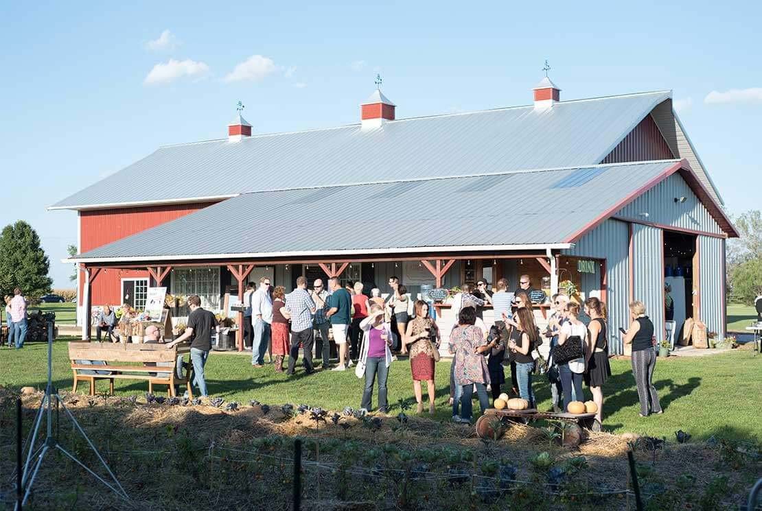A group of guests mingles at Locavore Farm in Kankakee County, Illinois
