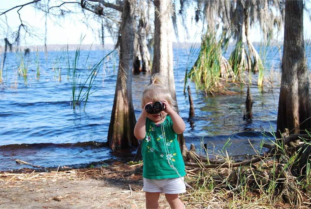 A toddler using binoculars at Disney Wilderness Preserve in Kissimmee, Florida