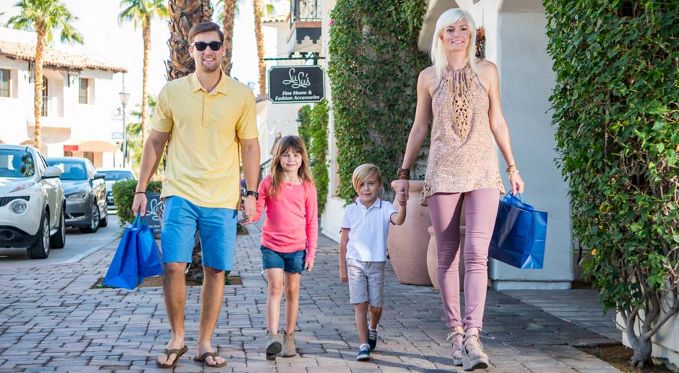 Two parents hold shopping bags and hold hands with their two young children as they walk down a brick shopping district road in La Quinta, CA