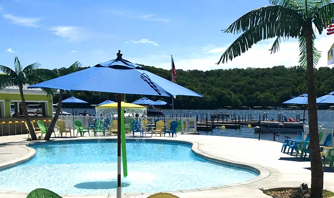 A small kids pools surrounded by blue umbrellas overlooks the lake at The Coconuts Caribbean Beach Bar & Grill in Lake of the Ozarks, MO