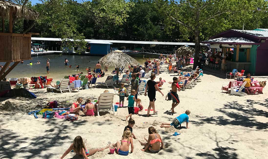 Beachgoers fill the beach, sitting on the sand and in beach chairs, at Franky & Louie's Beachfront Bar and Grill in Lake of the Ozarks, MO