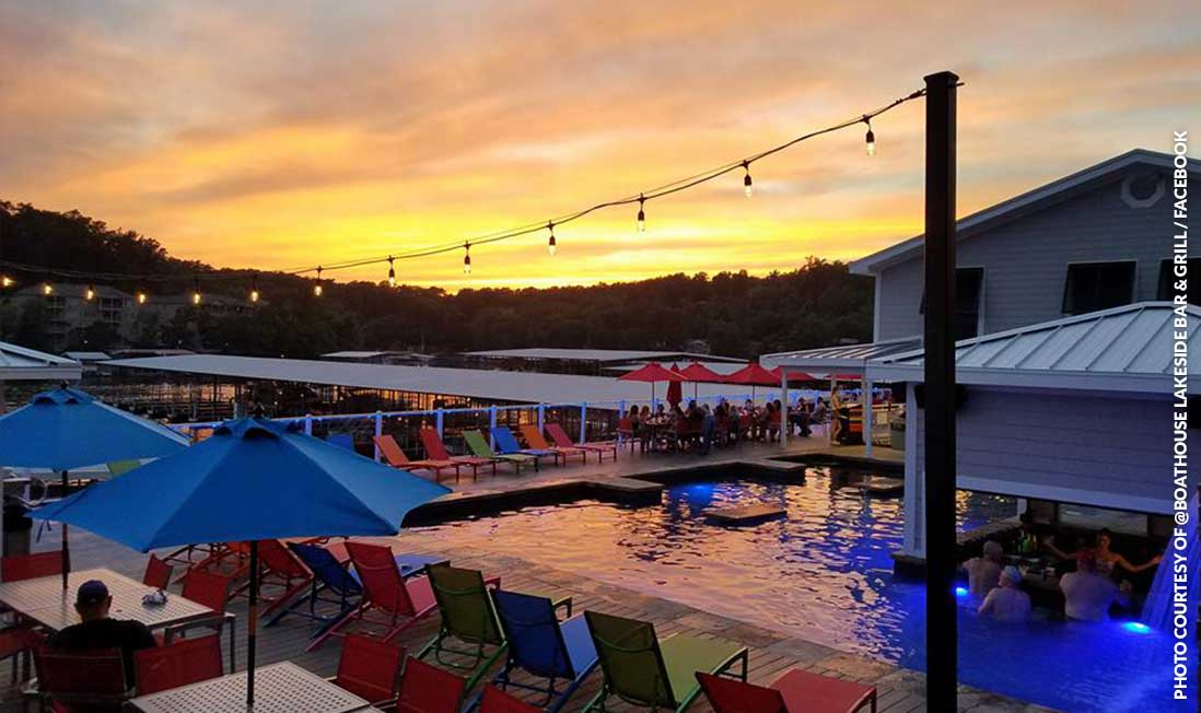 A lakeside pool surrounded by deck chairs, shown in front of a yellow sunset at Boathouse Lakeside Bar & Grill in Lake of the Ozarks, MO