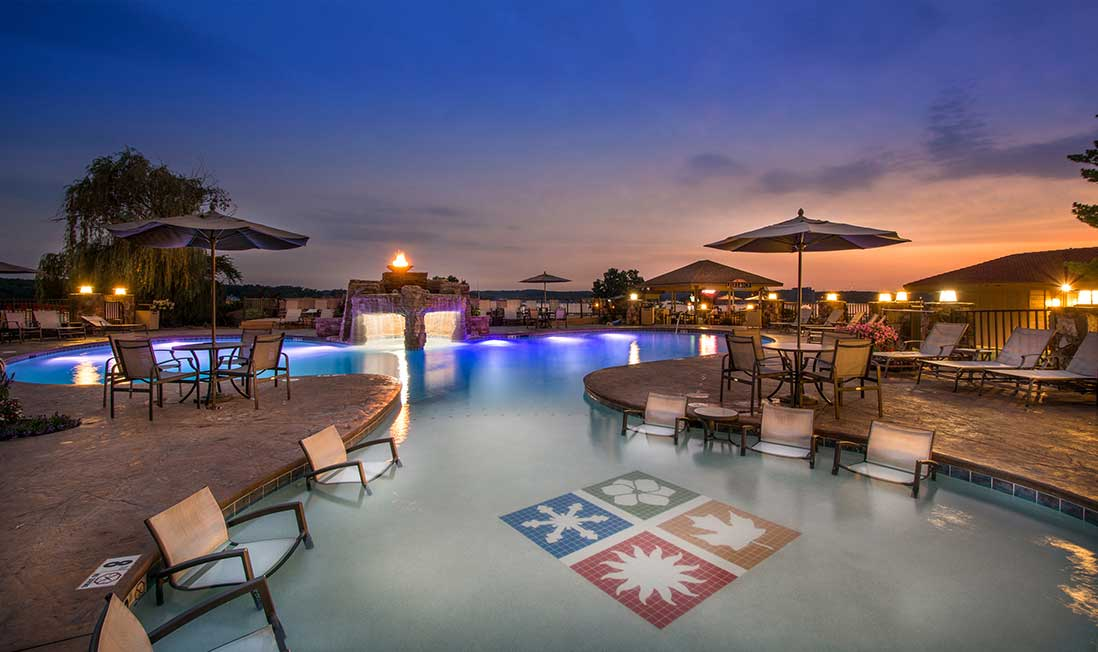 A lakeside pool at sunset, with in-pool lights and chairs, surrounded by round tables with chairs and umbrellas on the deck at Lodge of Four Seasons in Lake of the Ozarks, MO