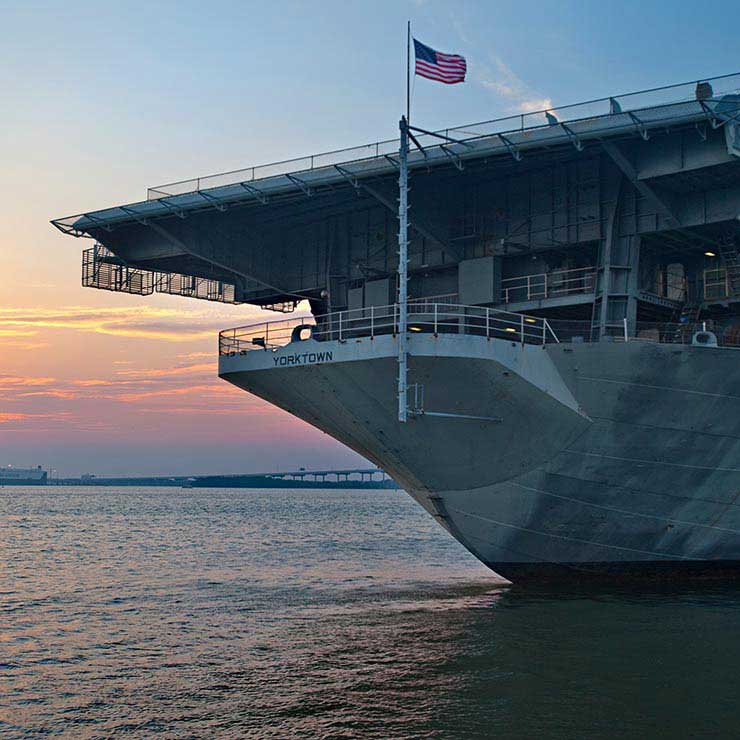 The U.S. flag flying from the USS Yorktown with the sun setting in the background in Mount Pleasant, South Carolina