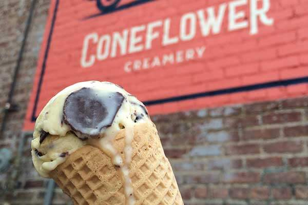An ice cream cone in front of the sign for Coneflower Creamery in the Blackstone District of Omaha, Nebraska