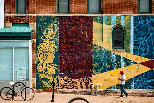 A man with a red hat walks in front of the Magic City mural in Omaha, Nebraska