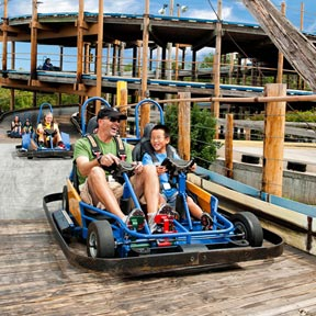 A father and son ride a black and blue go-kart on a wooden track at Track Family Fun Parks in Branson, Missouri