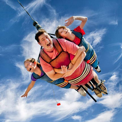 A father and two children on the Skycoaster at Track Family Fun Parks in Branson, Missouri