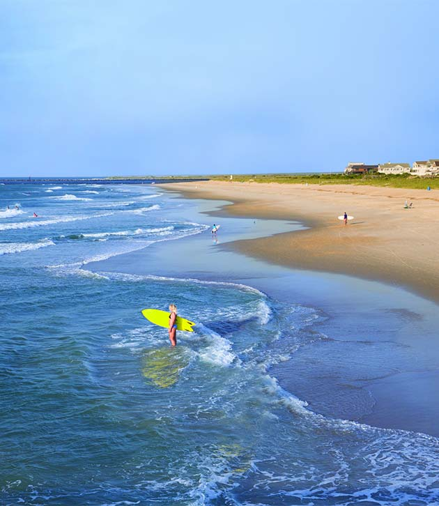 A Woman Stands In The Surf Holding Bright Yellow Surfboard Wrightsville Beach North