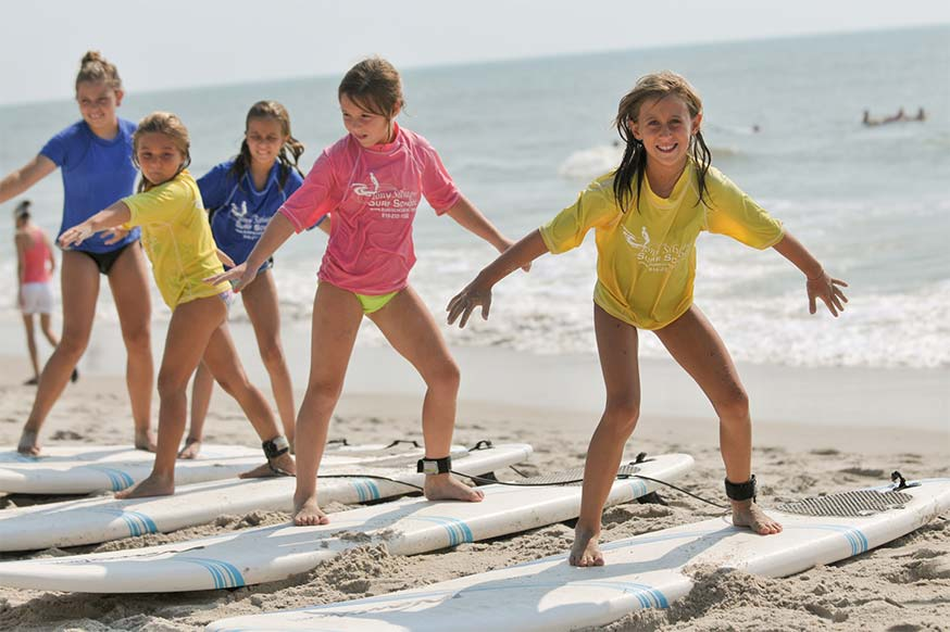 A group of young girls balance on surfboards on the sand at Tony Silvagni Surf School in Carolina Beach, North Carolina