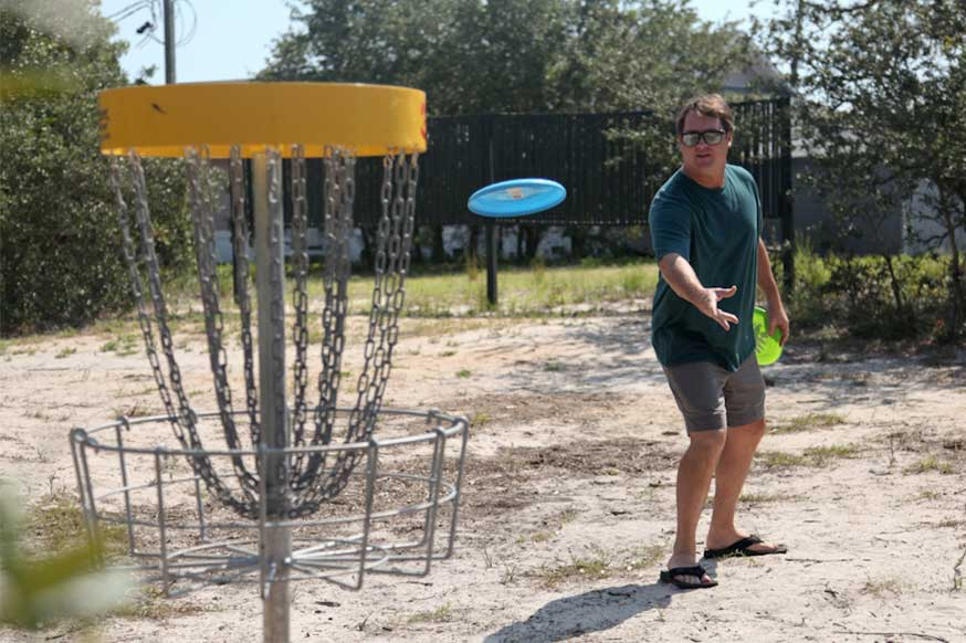 A man in shorts tosses a Frisbee during a game of disc golf in Carolina Beach, North Carolina