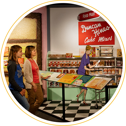 Visitors examining a food mart display at the Duncan Hines exhibit in the Kentucky Museum in Bowling Green, KY