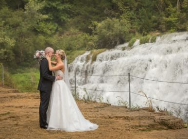Couple poses in front of a waterfall