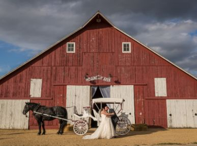 Couple kisses outside of a barn