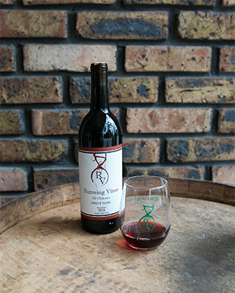 A bottle of wine and a glass of wine sit on a wooden barrel in front of a brick wall in Indiana Dunes, Indiana