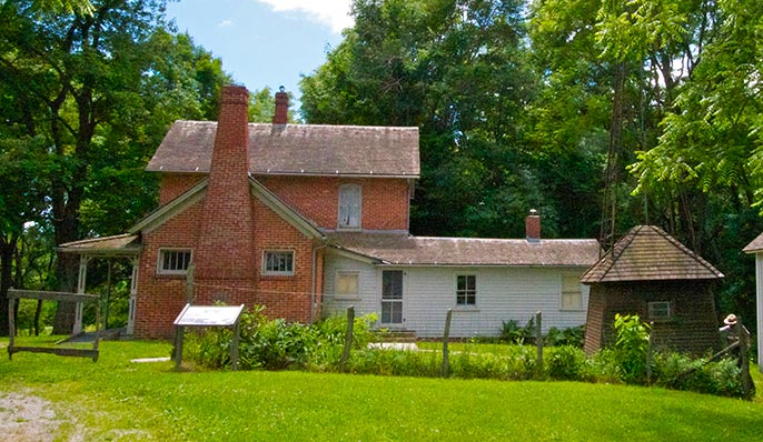The red brick and  white clapboard Chellberg Farmstead surrounded by a green lawn in Indiana Dunes, Indiana