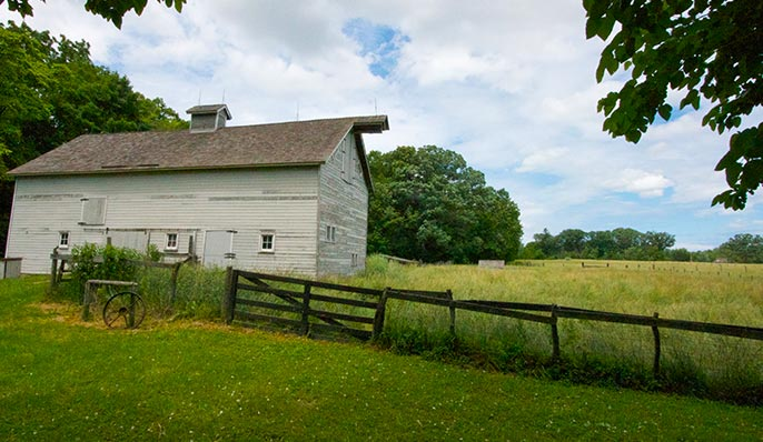 The white clapboard  Chellberg Farmstead surrounded by green grass and a wooden fence in Indiana Dunes, Indiana