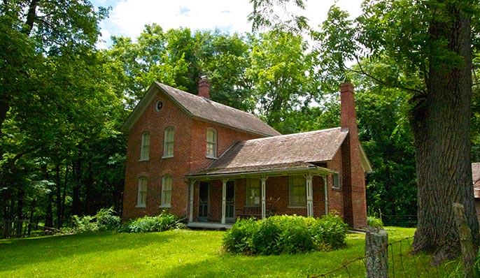 A two-story red brick  Chellberg Farmstead house surrounded by tall green trees and a lush green lawn in Indiana Dunes, Indiana
