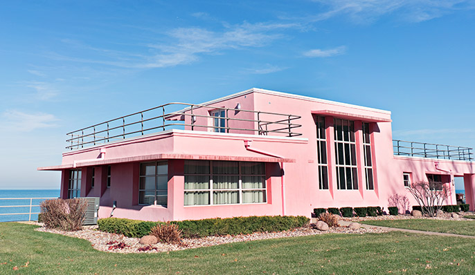 A pink mid-century home surrounded by a green lawn on the Century of Progress home tour in Indiana Dunes, Indiana