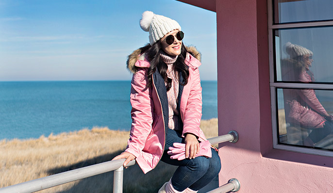 A woman in a pink coat  and white knit hat sits on a metal guardrail attached to a pink house on the Century of Progress tour in Indiana Dunes, Indiana