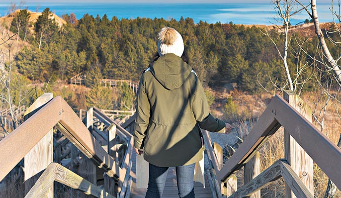 A woman in an olive  green jacket and a white knit hat stands on a wooden staircase overlooking Lake Michigan in Indiana Dunes, Indiana