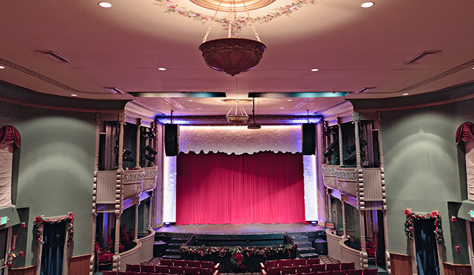 The interior of the Memorial Opera House with Christmas garlands, light green walls and a red curtain in Indiana Dunes, Indiana