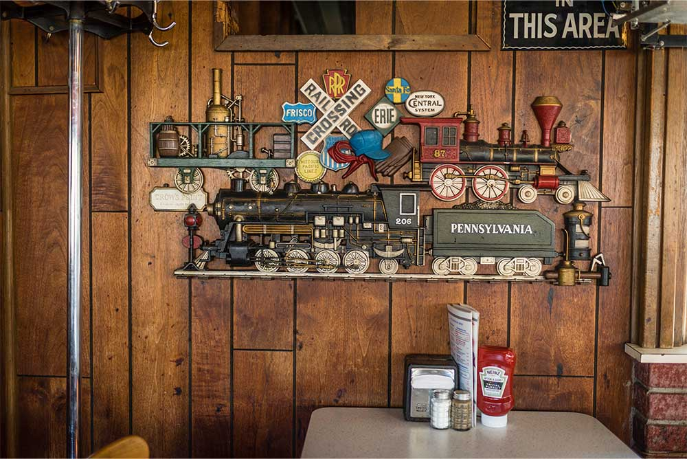 Train-themed artwork adorns a wooden-paneled wall above a dining table at Fritz's Railroad Restaurant in Kansas City, KS