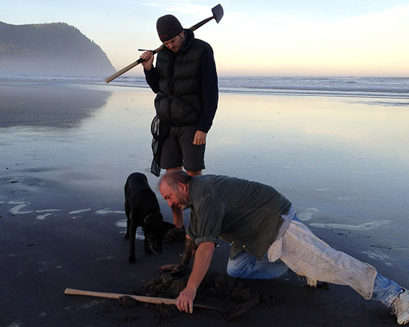Two men with a dog on the Seaside, Oregon beach digging for razor clams.