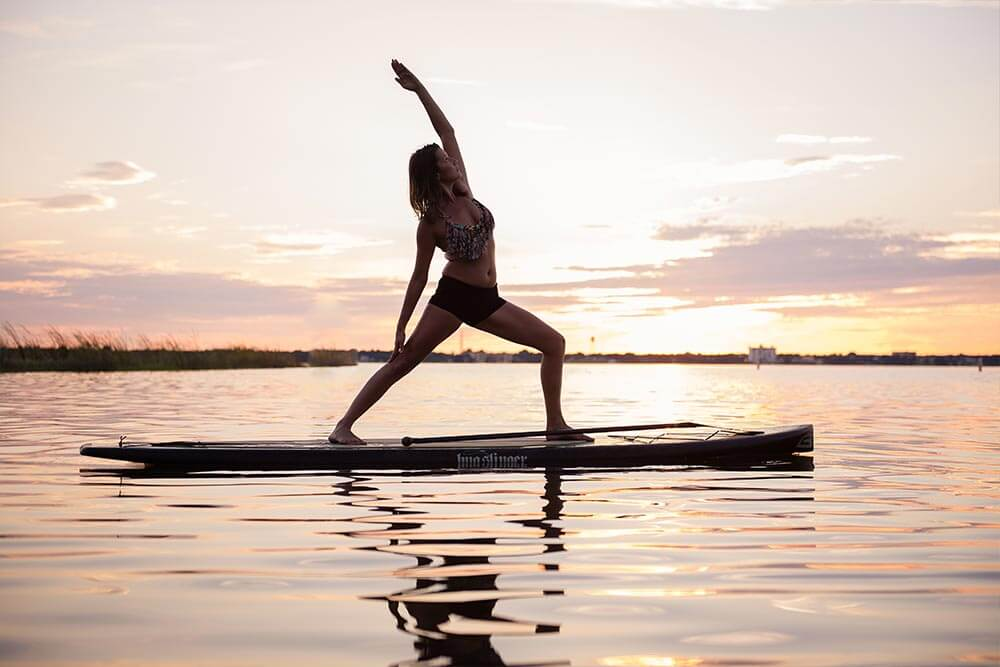 A woman in the reverse warrior pose does paddle board yoga on a lake in Sebring, Florida