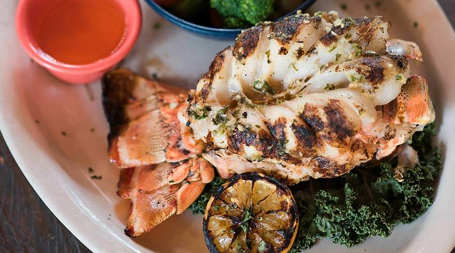 A lobster tail on a plate garnished with grilled lemon and melted butter at Cowpoke's Watering Hole restaurant and tiki bar in Sebring, Florida