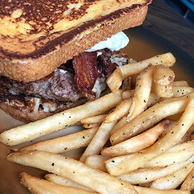 A grilled sandwich containing bacon accentuates a helping of French fries in Stillwater, MN.