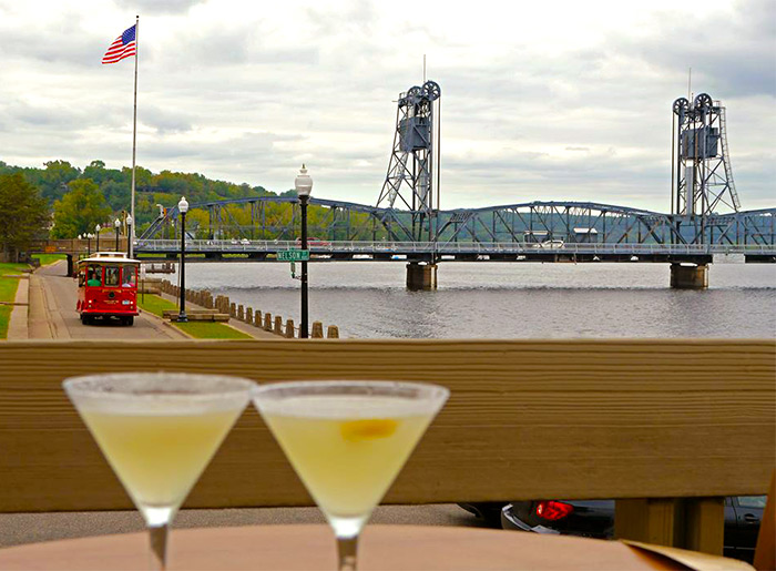 A bridge spans a body of water and ends beside a flagpole with the American flag and a trolley car running nearby, with a pair of mixed drinks in martini glasses in the foreground in Stillwater, MN.