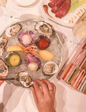 A photo of a dish of oysters served on ice with dipping sauces at Bern's Steak House in Tampa Bay, Florida