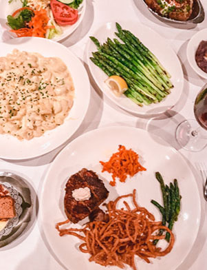 White dishes of food on a white tablecloth at Bern's Steak House in Tampa Bay, Florida