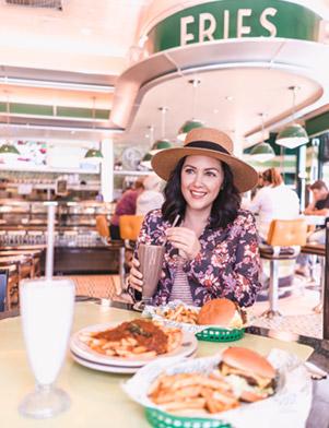 Influencer Ashley Buchanan holds a chocolate milkshake, sitting at a table with hamburgers at Goody Goody in Tampa Bay, Florida