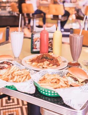Baskets of hamburgers and french fries, tall milkshakes and ketchup and mustard on a table at Goody Goody in Tampa Bay, Florida