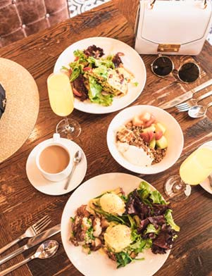 White plates of food on a brown wooden table at The Epicurean in Tampa Bay, Florida